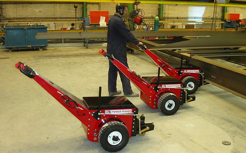 Power Pushers, with bespoke attachments, pushing steel fabrications on a rail-based production line